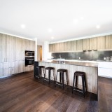 Clean-wooden-cabinets-with-wooden-flooring-and-stools-with-counter