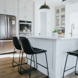 Kitchen-with-wooden-flooring-with-white-cabinets-and-black-chairs