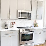 White-kitchen-Cabinets-with-wooden-flooring-and-white-wall-tiles
