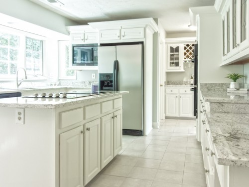 kitchen-with-island-at-centre-and-white-tiles-on-flooring.jpg
