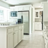 kitchen-with-island-at-centre-and-white-tiles-on-flooring