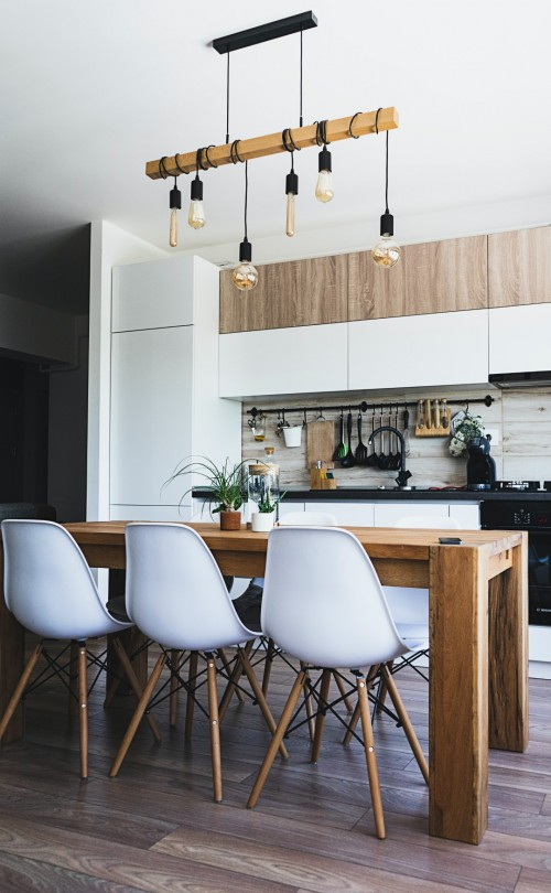 wooden-table-at-the-centre-of-kitchen-with-white-colored-cabinets-and-chairs.jpg