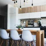 wooden-table-at-the-centre-of-kitchen-with-white-colored-cabinets-and-chairs