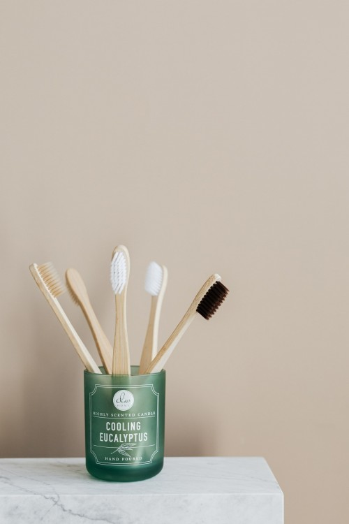 Bamboo-toothbrushes-in-green-holder-on-marble-table.jpg