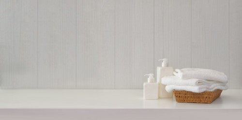 Bathroom-interior-with-soap-dispensers-and-towels-on-white-table.jpg