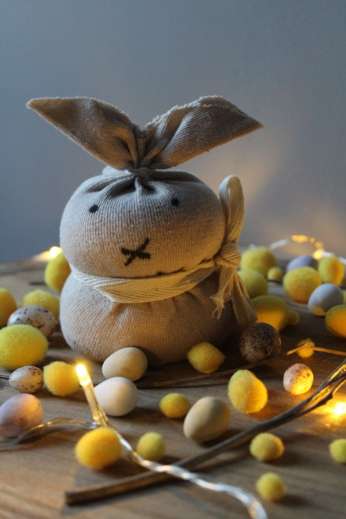 Easter-Bunny-toy-placed-on-table-among-scattered-decorative-eggs.jpg