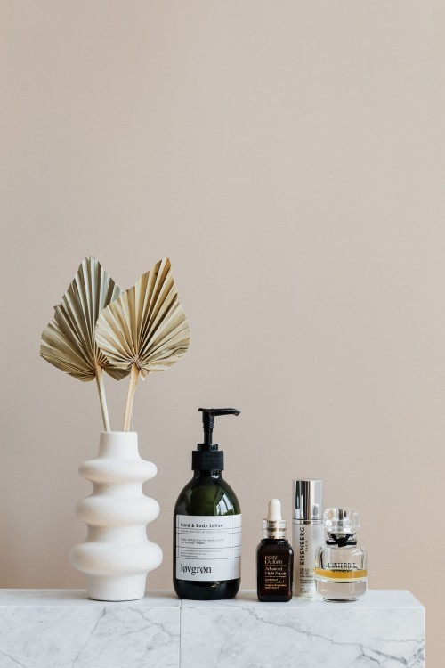 Set-of-cosmetic-supplies-near-decorative-leaves-in-vase-on-marble-shelf.jpg