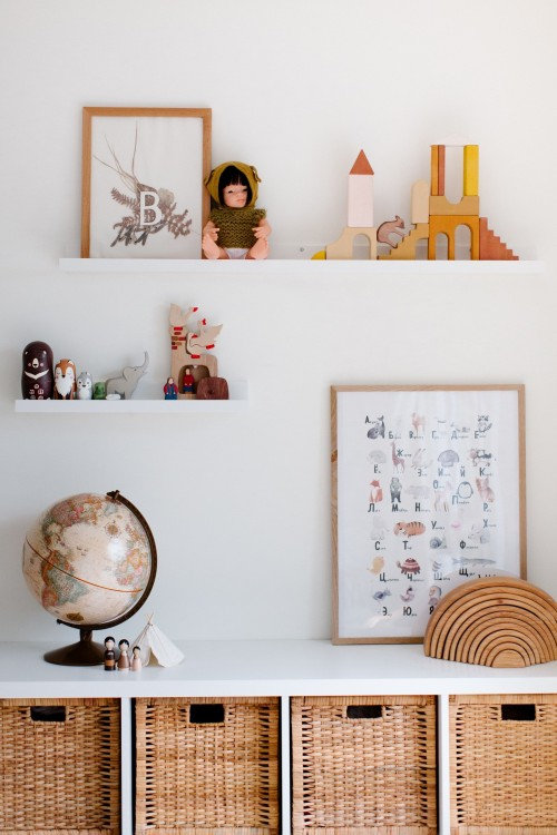 Vintage-glove-on-cabinet-with-toys-and-paintings-on-shelves-at-home.jpg
