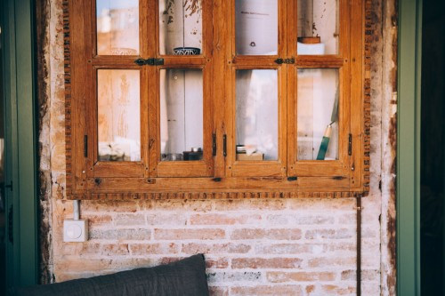 A-rustic-window-in-front-of-exposed-brick-holds-a-few-provides-a-home-for-the-curios..jpg