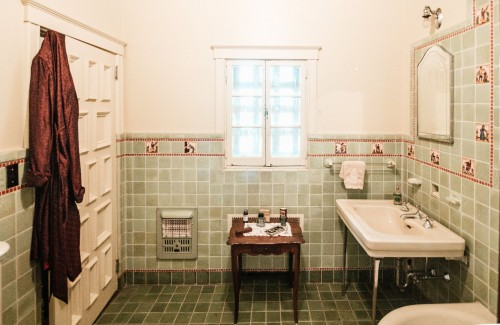 A-silk-robe-hangs-on-a-bathroom-door-while-toiletries-have-been-placed-on-an-ornate-table..jpg