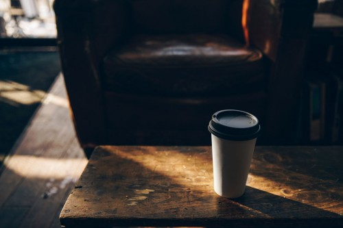 A-white-to-go-coffee-cup-sits-on-a-wooden-table.-The-leather-chair-in-the-background-gives-a-rustic-feel-to-this-cafe..jpg