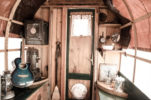 Inside-a-caravan-the-sun-streams-in-through-the-windows-to-illuminate-a-guitar-and-a-lantern-amidst-other-fairly-rustic-objects..jpg