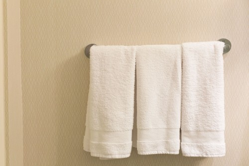 Three-hotel-towels-are-hung-on-a-rack-against-a-wall.-These-are-the-perfect-type-of-towels-to-use-after-a-relaxing-bath..jpg