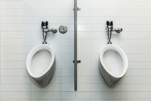 Two-urinals-in-a-public-restroom-placed-side-by-side-against-a-white-tile-wall..jpg