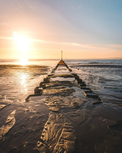 A-golden-sunset-burrows-into-the-horizon-of-a-ruined-pier-a-sculptured-arrow-stands-at-its-end-pointing-into-the-fading-sky..jpg