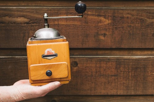 A-hand-holds-up-a-yellow-antique-coffee-grinder-against-a-wooden-wall.jpg