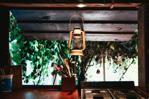 The-open-window-behind-a-rustic-kitchen-counter-and-stove-looks-out-onto-jungle-foliage.-A-lantern-hangs-over-the-surface-on-which-sits-a-container-of-kitchen-utensils..jpg