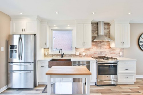 silver-refrigerator-beside-wooden-sink-and-wooden-table-at-the-center-of-kitchen.jpg