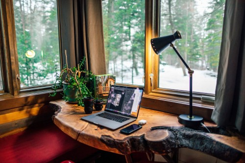 black-and-gray-laptop-computer-beside-black-smartphone-and-black-table-lamp-on-wooden-table-near-window.jpg
