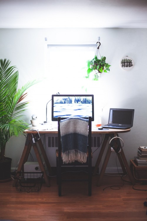 black-flat-screen-computer-monitor-on-brown-wooden-table-on-brown-wooden-floor-inside-the-room.jpg