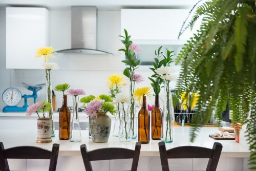 green-leafed-plants-in-bowl-and-bottles-on-top-of-white-wooden-table.jpg