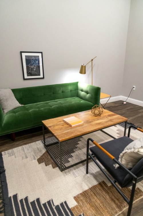 green-sofa-and-black-chair-beside-brown-wooden-table-and-silver-color-lamp-inside-a-green-sofa-near-white-wall.jpg