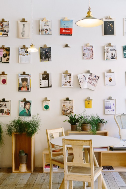 magazines-hanged-on-wall-near-round-beige-wooden-table-with-chairs.jpg