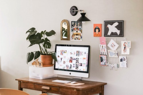 silver-iMac-on-brown-wooden-desk-and-imagewallpaper-and-mirror-on-white-wall-inside-the-room.jpg
