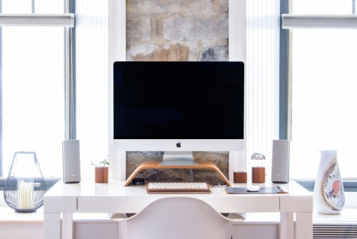 white-iMac-with-speaker-on-top-white-desk-and-chair-near-window.jpg