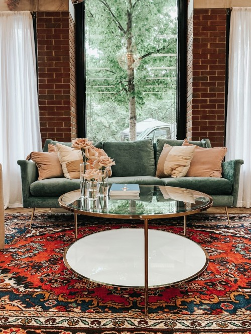 brown-pillows-on-sofa-with-round-glass-table-on-carpet-near-window-inside-living-room.jpg