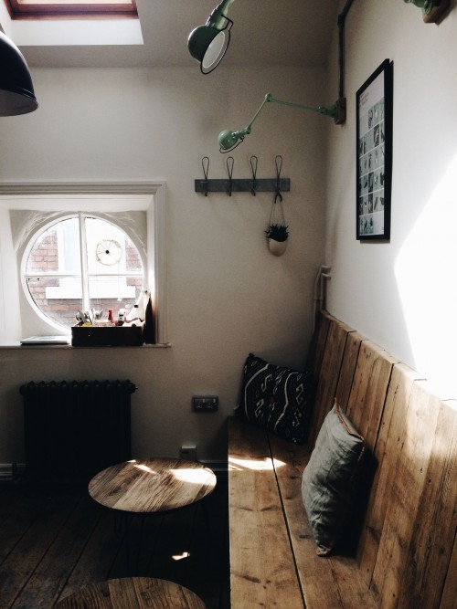 brown-wooden-bench-beside-white-painted-wall-with-hanger--frame--lamp-and-round-window-inside-the-room.jpg