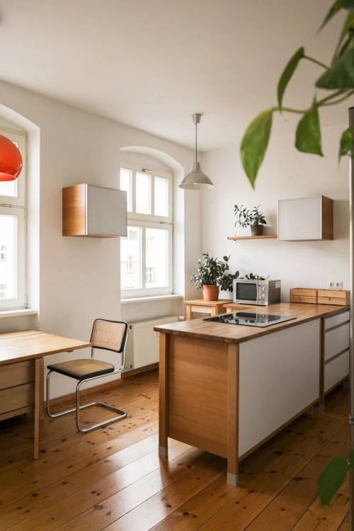 brown-wooden-desk-with-chair-on-wooden-surface-and-oven-and-plant-pot-on-wooden-counter-near-window.jpg