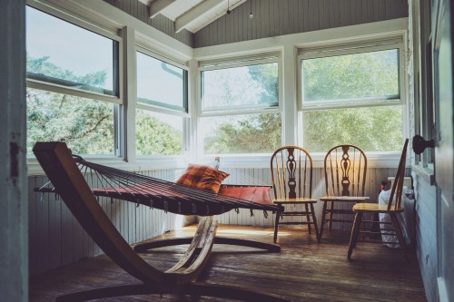 brown-wooden-house-interior-with-three-brown-wooden-Windsor-chairs-beside-brown-hammock-with-glass-windows-inside-the-room.jpg
