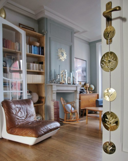 gold-colored-wind-chimes-on-white-door-and-wooden-drawer-behind-a-leader-chair-photo.jpg