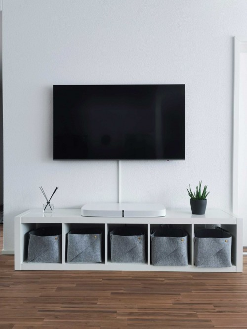 turned-off-flat-screen-TV-and-rack-on-white-wall-and-wooden-floor-inside-the-room.jpg