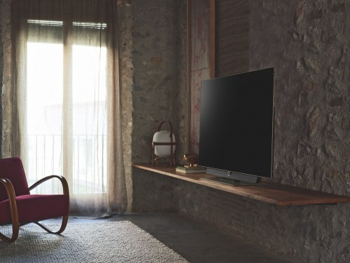 turned-off-flat-screen-television-on-brown-wooden-TV-stand-inside-red-cover-wooden-chair-near-window.jpg