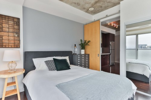 white-bed-linen-near-brown-wooden-door-with-white-and-black-bed-in-badrrom.jpg