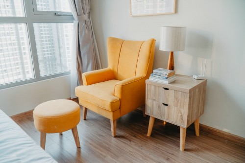 yellow-armchair-and-wooden-stool-beside-round-shape-wihte-wooden-nightstand-by-the-wall-inside-the-room.jpg