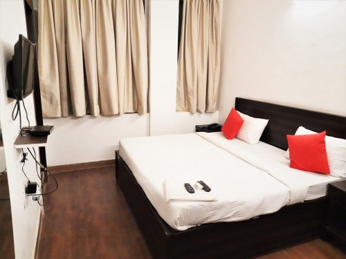 black-flat-screen-tv-on-white-wall-and-white-bed-with-thrown-pillow-with-white-bed-linen-photo.jpg