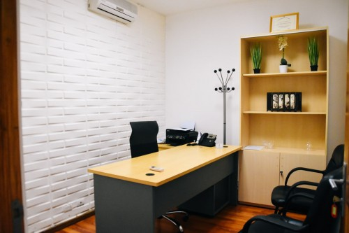 black-office-rolling-chair-beside-brown-wooden-table-near-white-wall-and-wooden-shelf-inside-home-office-room.jpg