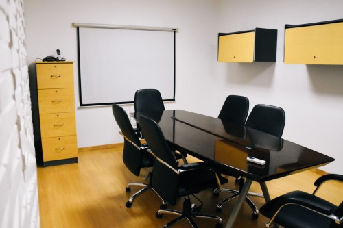 black-table-with-black-rolling-chair-on-yellow-sirface-and-black-and-white-drawer-on-white-wall-inside-home-office.jpg
