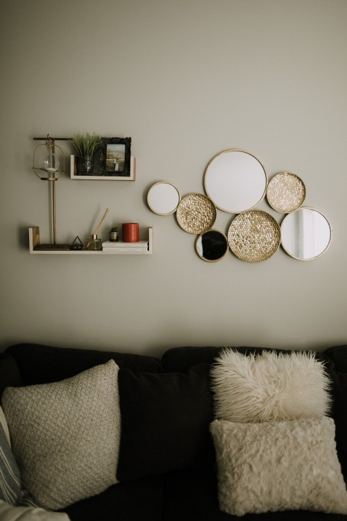 black-throw-pillow-on-black-couch-and-shelf-on-white-wall-and-spherical-mirror-frame-on-wall.jpg