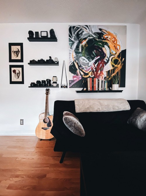brown-acoustic-guitar-beside-black-couch-and-black-shelf-and-colored-painting-on-white-wall-inside-living-room-boho-interior-photo.jpg