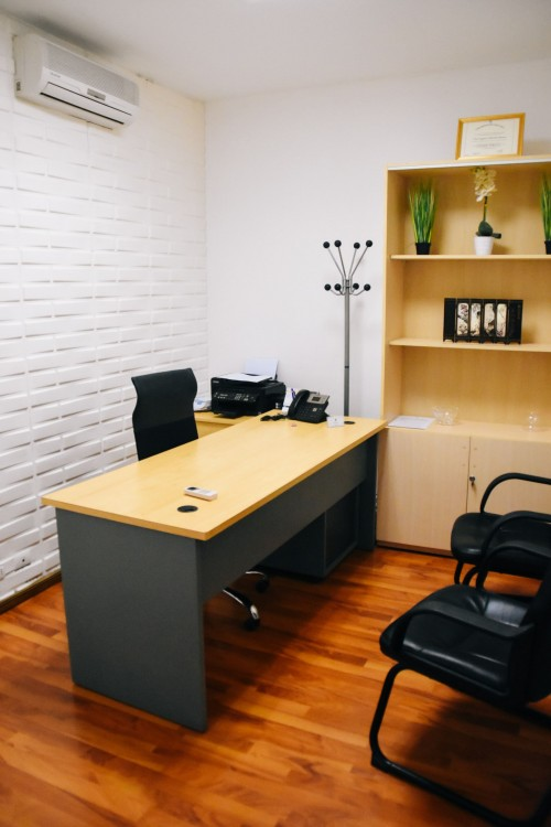 brown-and-black-wooden-desk-with-black-leader-chair-on-brown-wooden-surface-and-wooden-shelf-inside-desk-photo.jpg