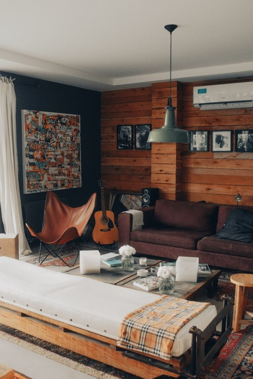 brown-sofa-near-white-table-and-stool-beside-guitar-near-wooden-wall-living-room.jpg