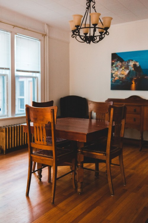 brown-wooden-dining-table-and-chairs-on-brown-surface-near-window-and-painting-on-wall-inside-dining-room-photo.jpg