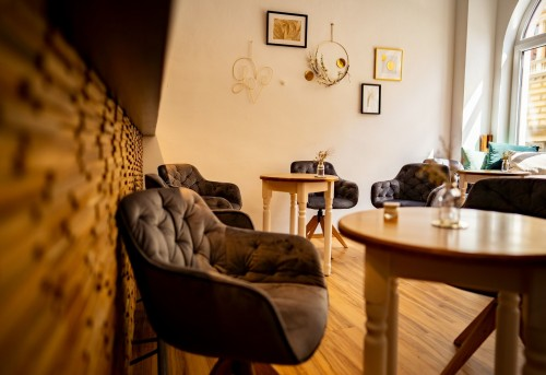 brown-wooden-table-beside-brown-wooden-chair-near-wooden-designed-wall-and-frame-on-it-boho-interior.jpg