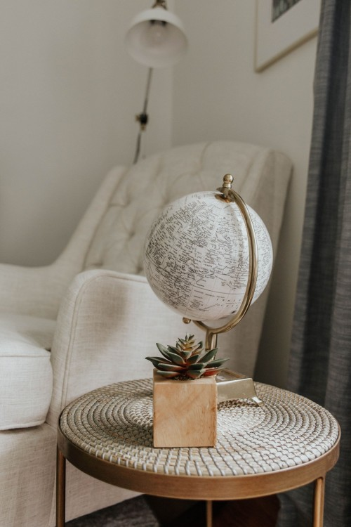 globe-and-plant-pot-on-brown-table-beside-white-sofa-chair-near-curtain-living-room-photo.jpg