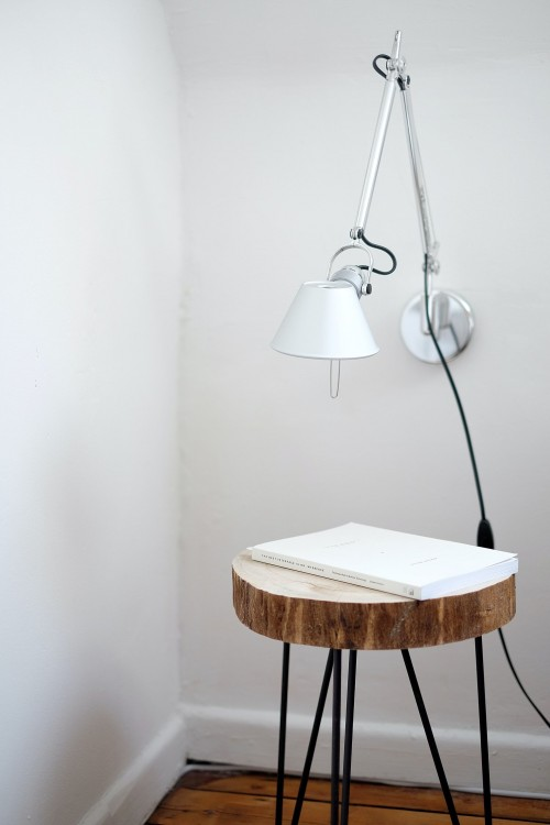 gray-desk-lamp-mount-on-white-wall-under-brown-stool-with-white-book-on-top-near-white-wall-corner-nodern-interior-photo.jpg