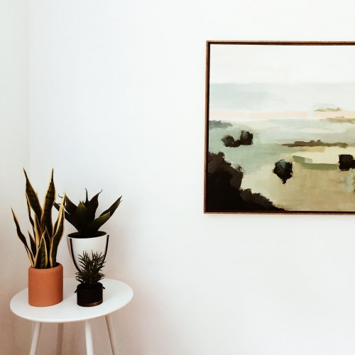 green-and-brown-tree-on-white-table-near-body-of-water-painting-on-white-wall-photo.jpg